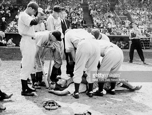 Brooklyn Dodger's catcher Babe Phelps is surrounded by teammates after being hit by a foul tip during game with the Pittsburgh Pirates at Ebbet's...