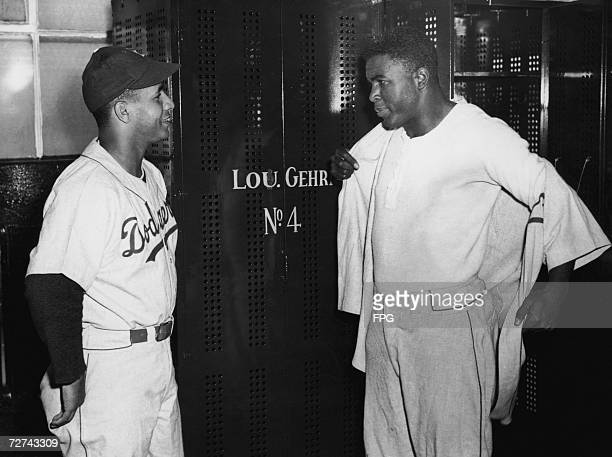 Brooklyn Dodgers catcher Roy Campenella left and second baseman Jackie Robinson get dressed before a preseason exhibition game with the Yankees at...