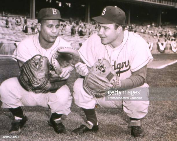 Brooklyn Dodger catchers Roy Campanella left and Joe Pignatano compare mitts before a game in 1953 at Ebbets Field in Brookly New York