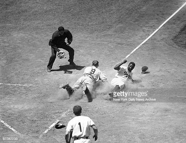 Brooklyn Dodgers' Jackie Robinson kicks up dust as he slides across the plate to steal home against the New York Giants.