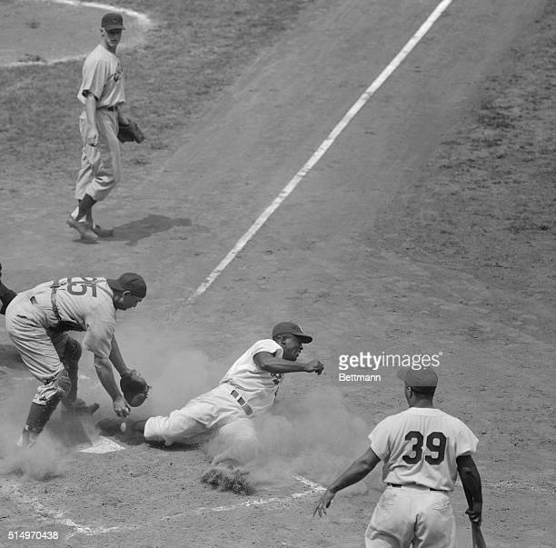 Brooklyn Dodgers Jackie Robinson shifted to second base for the July 27th game with the Chicago Cubs slides safely into home plate on a second inning...