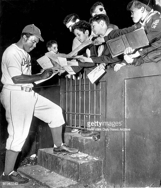 Brooklyn Dodgers' Jackie Robinson signs autographs for fans between innings.