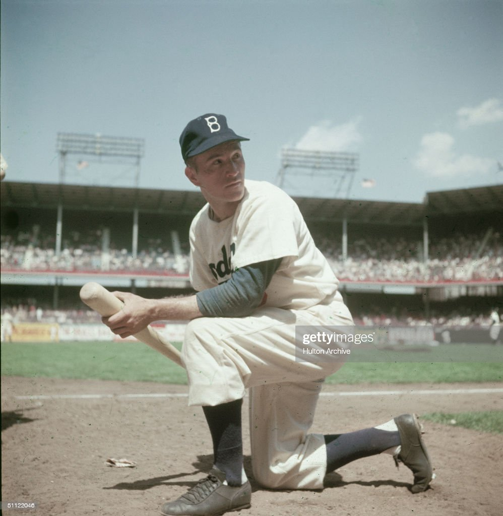 Brooklyn Dodgers outfielder George Shuba kneels on the baseball diamond, holding a bat, early 1950s.