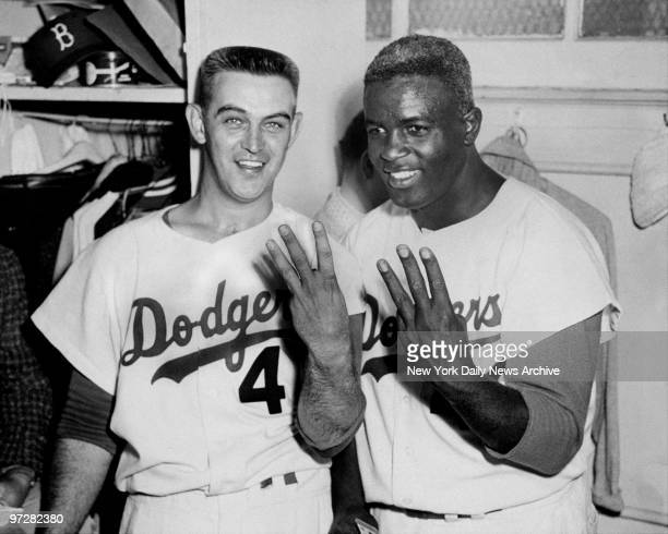 Brooklyn Dodgers' pitcher Clem Labine and Jackie Robinson in locker room during World Series They're both holding up three fingers indicating the 33...