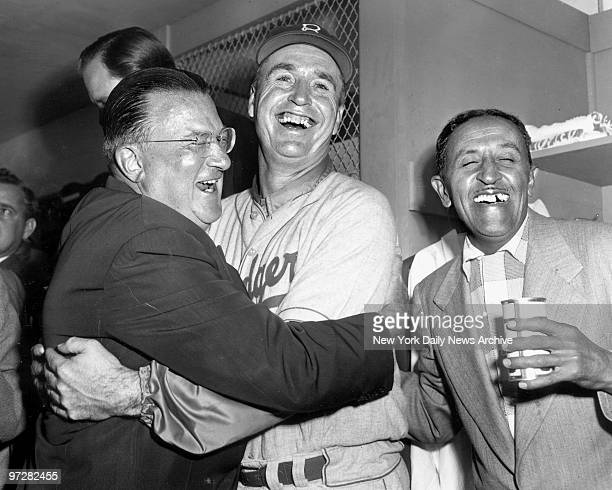 Brooklyn Dodgers president Walter O'Malley and his manager Walter Alston exchange hugs and grins after bringing Brooklyn its first World Series...