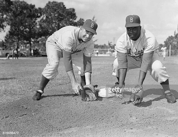 Brooklyn Dodgers' Randy Jackson and Jackie Robinson rivals for the third base slot each keep a foot down on third as they practice here at Dodgertown...