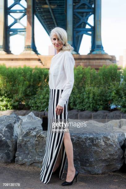 USA, Brooklyn, Dumbo, stylish mature woman standing in front of Manhattan Bridge
