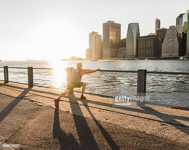 usa, brooklyn, man doing stretching exercises in front of manhattan skyline in the evening - man bending over from behind stock photos and pictures