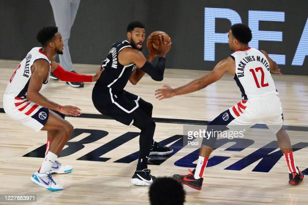 Brooklyn Nets guard Garrett Temple holds the ball while defended by Washington Wizards forward Troy Brown Jr #6 and guard Jerome Robinson in the...