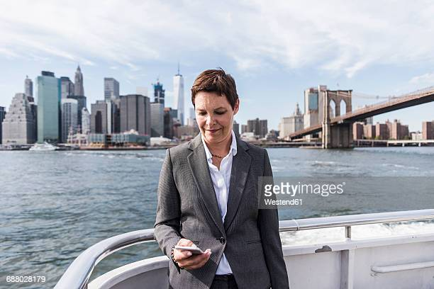 usa, brooklyn, portrait of businesswoman standing on boat looking at cell phone - ship front view stock-fotos und bilder