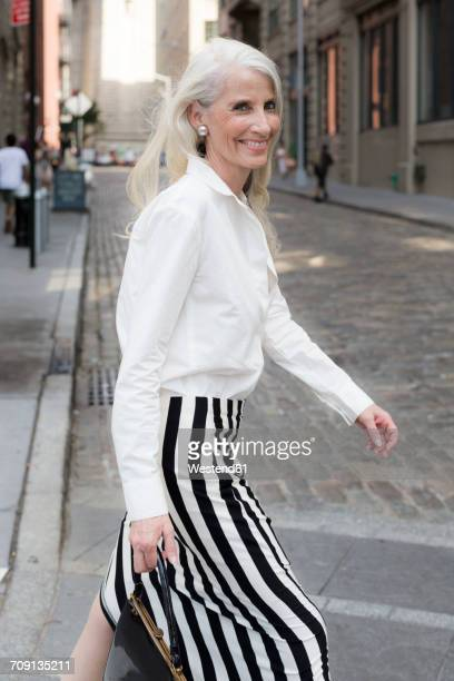 usa, brooklyn, portrait of smiling mature woman crossing the street - bluse stock-fotos und bilder