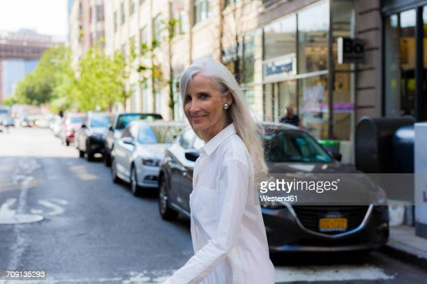 usa, brooklyn, portrait of smiling mature woman crossing the street - white hair stock pictures, royalty-free photos & images