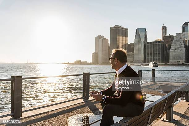 USA, Brooklyn, relaxed man with smartphone sitting on bench looking at view