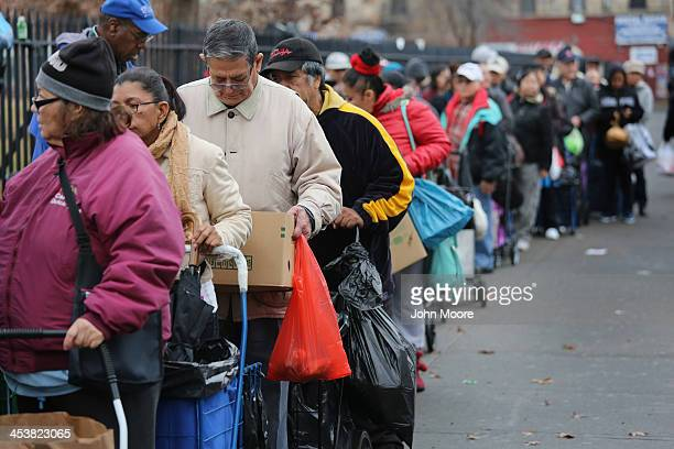 Brooklyn residents receive free food as part of a Bowery Mission outreach program on December 5 2013 in the Brooklyn borough of New York City The...