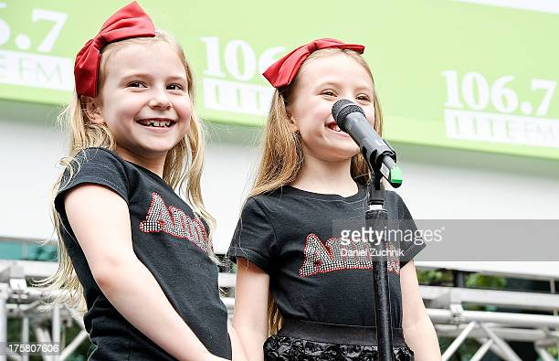 Brooklyn Shuck and Emily Rosenfeld from the cast of 'Annie' perform during 1067 LITE FM's Broadway in Bryant Park 2013 at Bryant Park on August 8...