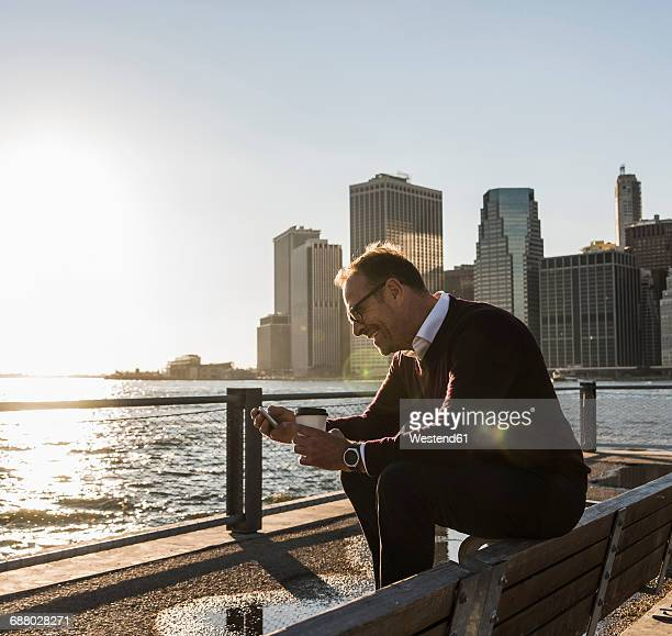 USA, Brooklyn, smiling man with coffee to go sitting on bench looking at smartphone
