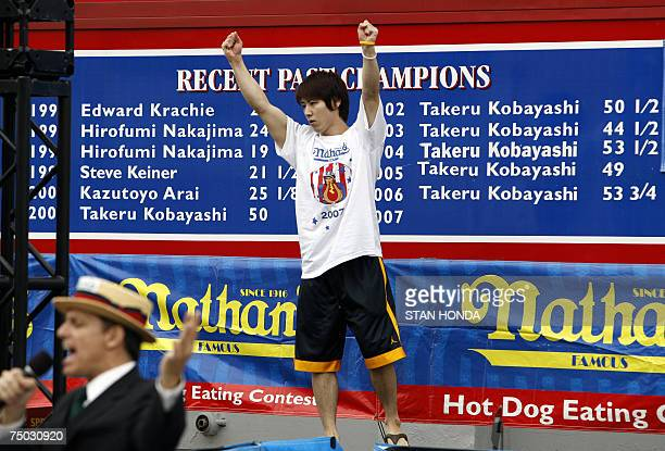 Takeru Kobayashi of Nagano Japan is introduced in front of a billboard showing his six consecutive wins and number of hot dogs ate during the annual...