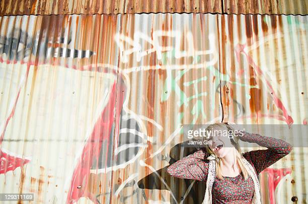 USA, Brooklyn, Williamsburg, Portrait of woman with headphones against graffiti wall