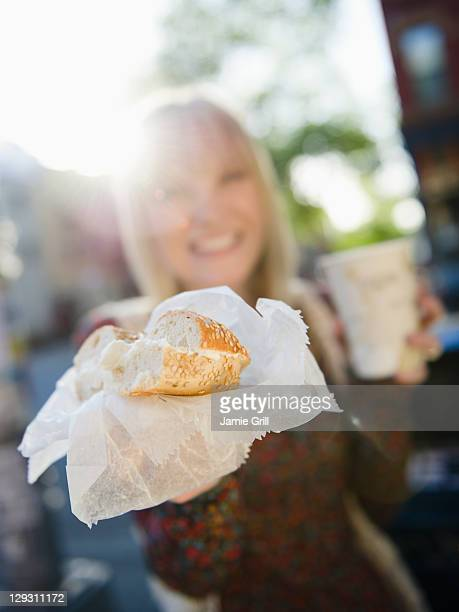 USA, Brooklyn, Williamsburg, Woman showing bagel