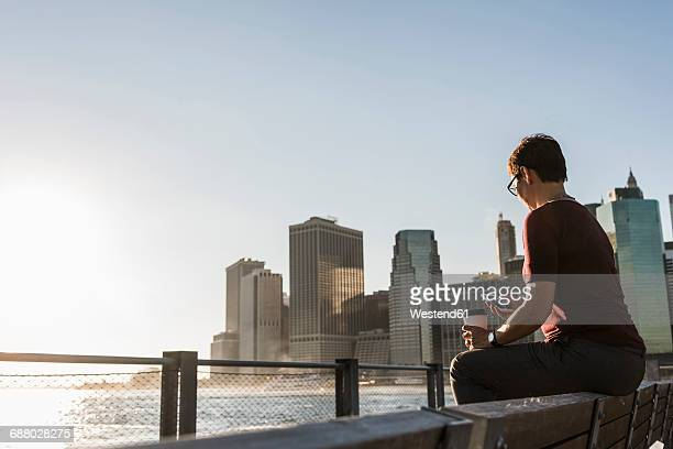USA, Brooklyn, woman with coffee to go sitting on bench looking at smartphone