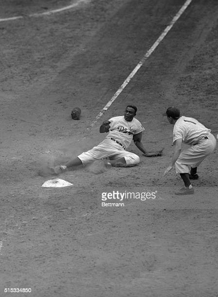 Brooklyn's Jackie Robinson slides in safely at home plate scoring from first base in the sixth inning of the clash with the New York Giants Catcher...