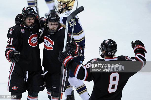 Brooks Bertsch, Joey Benik and Cory Thorson of the St. Cloud State Huskies celebrate a goal by Bertsch against the Notre Dame Fighting Irish during...