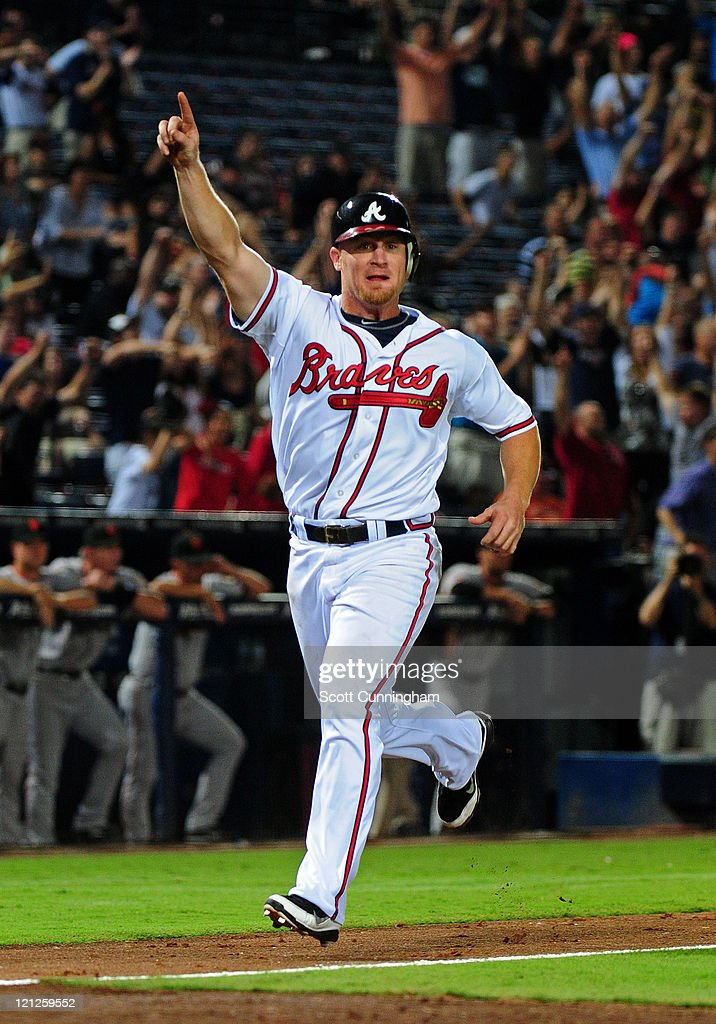 Brooks Conrad #7 of the Atlanta Braves celebrates as he scores the game-winning run against the San Francisco Giants at Turner Field on August 16, 2011 in Atlanta, Georgia.