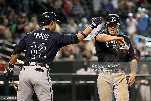 Brooks Conrad of the Atlanta Braves celebrates with teammate Martin Prado after scoring a run against the Arizona Diamondbacks during the ninth...