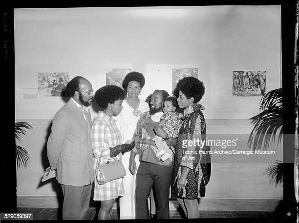 J Brooks Dendy III Brenda Joyce Jackson Thaddeus 'Thad' Mosley holding his baby Tereneh and Yvonne Reed Mosley standing near painting titled 'John...