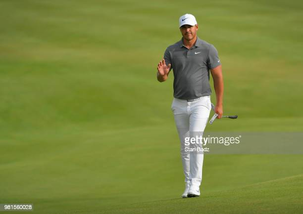 Brooks Koepka acknowledges the gallery walking along the 18th hole during the second round of the Travelers Championship at TPC River Highlands on...
