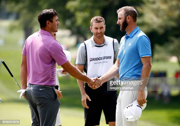 Brooks Koepka and Dustin Johnson shake hands on the ninth green during the first round of the World Golf Championships Bridgestone Invitational at...