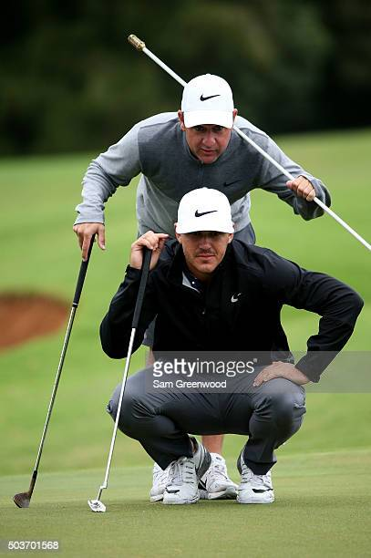 Brooks Koepka lines up a putt with caddie Ricky Elliott during the Hyundai Tournament of Champions ProAm at the Plantation Course at Kapalua Golf...