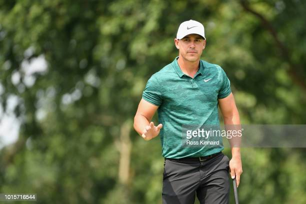 Brooks Koepka of the United States acknowledges the crowd after making a putt for birdie on the first green during the final round of the 2018 PGA...