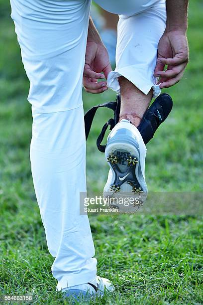 Brooks Koepka of the United States adjusts his shoe on the 18th hole during the second round of the 2016 PGA Championship at Baltusrol Golf Club on...
