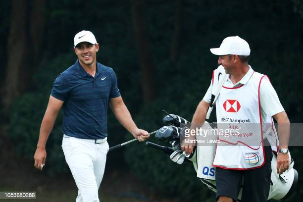 Brooks Koepka of the United States and 2018 Caddy of the Year Ricky Elliott react a chip in on the 15th hole during the second round of the WGC HSBC...