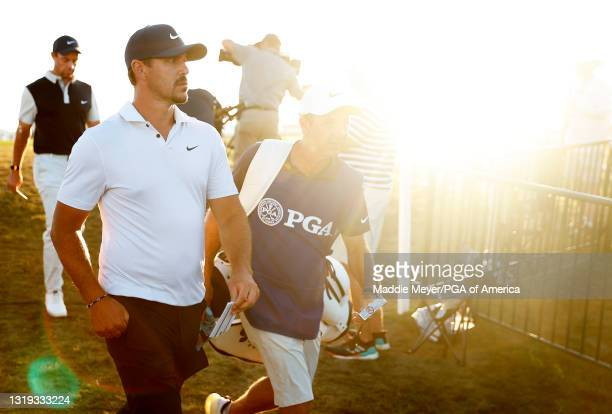 Brooks Koepka of the United States and caddie Ricky Elliott leave the 18th green during the second round of the 2021 PGA Championship at Kiawah...