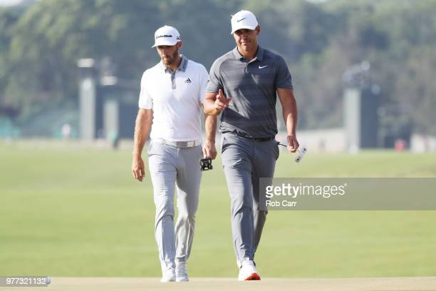 Brooks Koepka of the United States and Dustin Johnson of the United States walk off on the 18th green during the final round of the 2018 US Open at...