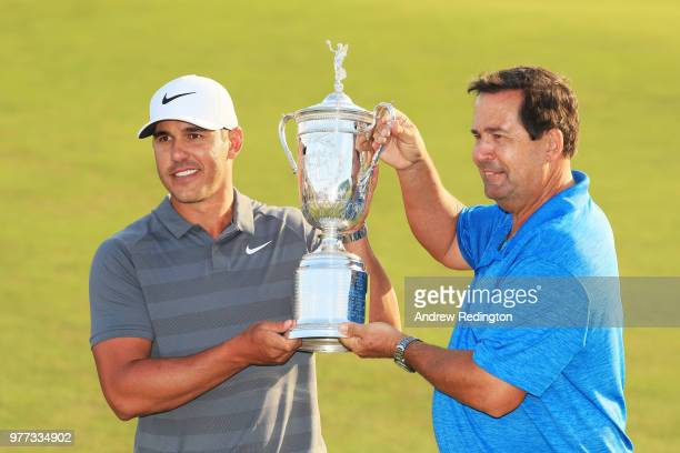 Brooks Koepka of the United States and his father Robert Koepka celebrate with the US Open Championship trophy after winning the 2018 US Open at...