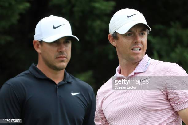 Brooks Koepka of the United States and Rory McIlroy of Northern Ireland look on from the eighth tee during the final round of the TOUR Championship...