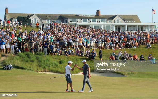 Brooks Koepka of the United States celebrates with caddie Richard Elliott on the 18th green during the final round of the 2018 US Open at Shinnecock...