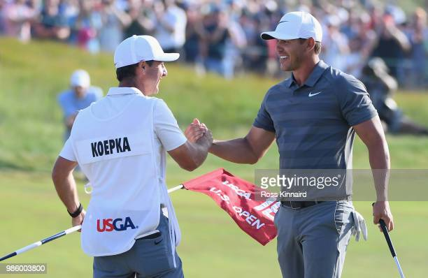 Brooks Koepka of the United States celebrates with caddie Richard Elliott on the 18th green during the final round of the 2018 U.S. Open at...
