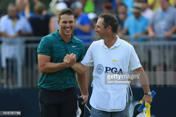 Brooks Koepka of the United States celebrates with caddie Ricky Elliott after winning the 2018 PGA Championship with a score of -16 at Bellerive...