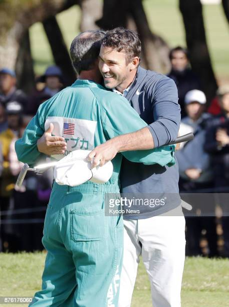 Brooks Koepka of the United States celebrates with his caddy after winning the Dunlop Phoenix golf tournament at Phoenix Country Club in Miyazaki on...