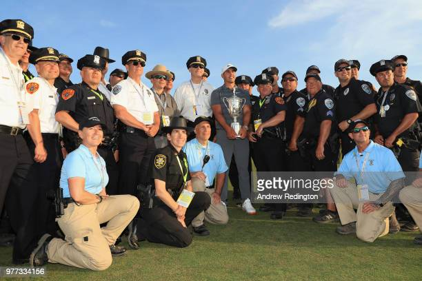 Brooks Koepka of the United States celebrates with police and security staff after winning the 2018 US Open at Shinnecock Hills Golf Club on June 17...