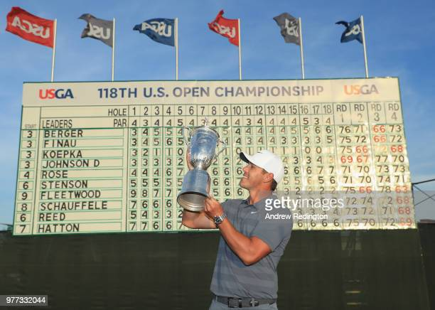 Brooks Koepka of the United States celebrates with the US Open Championship trophy in front of the final leaderboard after winning the 2018 US Open...