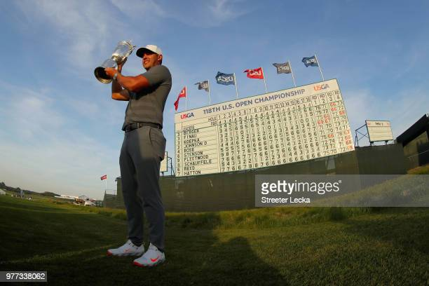 Brooks Koepka of the United States celebrates with the U.S. Open Championship trophy in front of the final leaderboard after winning the 2018 U.S....