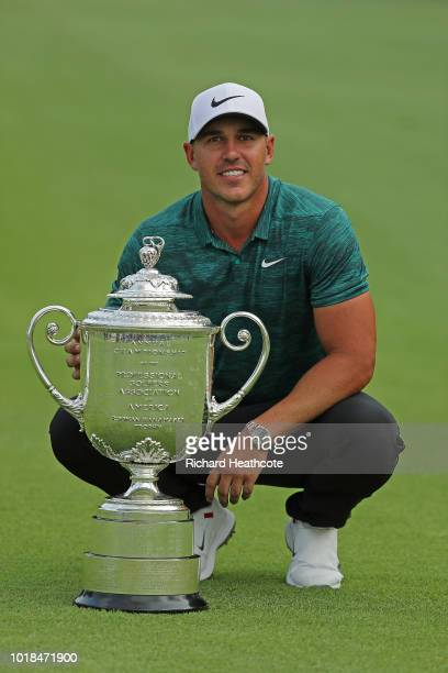 Brooks Koepka of the United States celebrates with the Wanamaker Trophy on the 18th green after winning the 2018 PGA Championship with a score of -16...