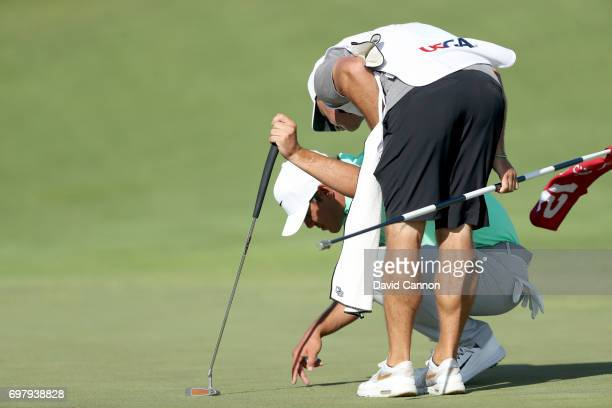 Brooks Koepka of the United States checks the green on the par 4 12th hole watched by his caddie Ricky Elliott during the final round of the 117th US...