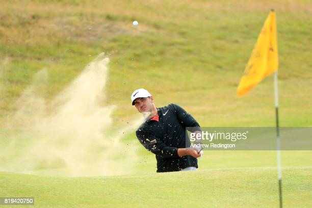 Brooks Koepka of the United States hits his third shot from the bunker on the 18th hole during the first round of the 146th Open Championship at...