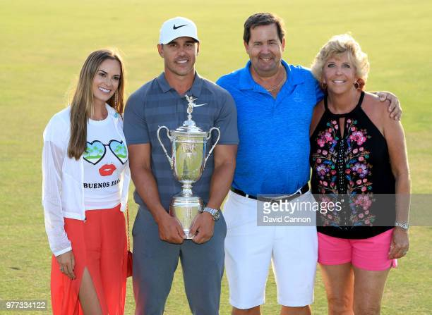 Brooks Koepka of the United States holds the trophy with his father Bob Koepka on Father's Day with his girlfriend Jena Sims and his mother Denise...